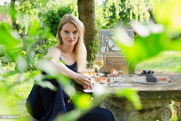 Portrait of mid adult woman sitting at picnic table in garden