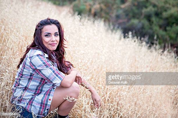 Portrait of mid adult woman sitting in long grass