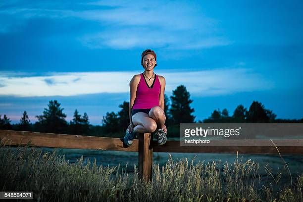 portrait of mid adult woman sitting on fence - heshphoto stock pictures, royalty-free photos & images