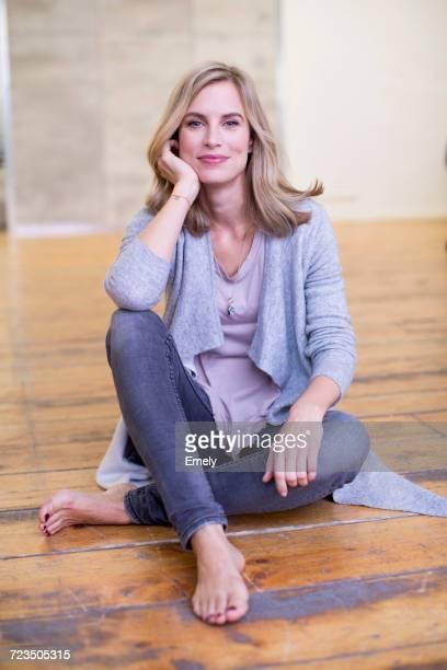 portrait of mid adult woman, sitting on floor, resting elbow on knee, smiling - kin in de hand stockfoto's en -beelden