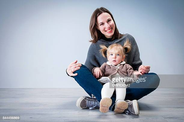 Portrait of mid adult woman sitting on floor with toddler daughter sitting on lap