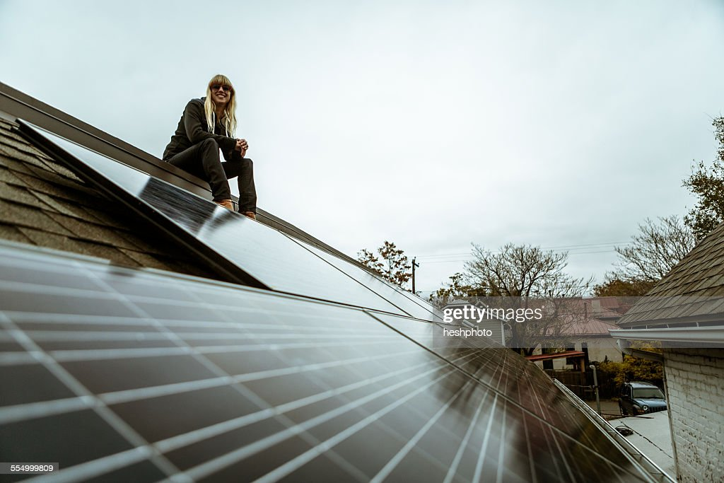 Portrait of mid adult woman sitting on newly solar paneled house roof : Stock Photo