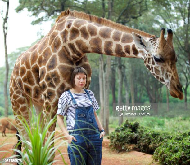 Portrait Of Mid Adult Woman Standing By Giraffe In Forest