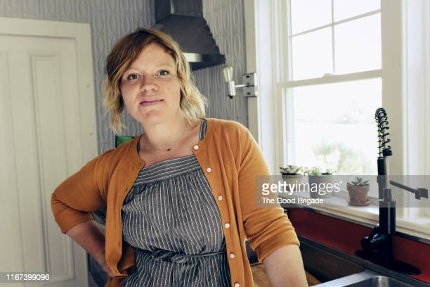 portrait of mid adult woman standing in kitchen - gente comum - fotografias e filmes do acervo