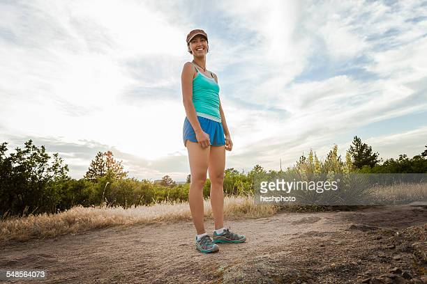 portrait of mid adult woman standing on dirt track - heshphoto stock pictures, royalty-free photos & images