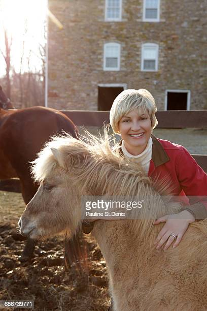 Portrait of mid adult woman standing with pony