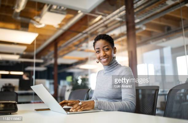 portrait of mid adult woman using laptop - portrait pro stock pictures, royalty-free photos & images