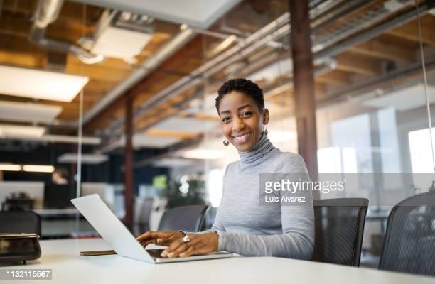portrait of mid adult woman using laptop - zugänglichkeit stock-fotos und bilder