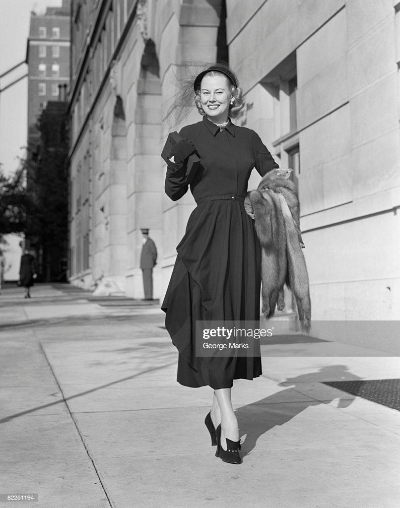 Portrait of mid adult woman walking along sidewalk : Stock Photo