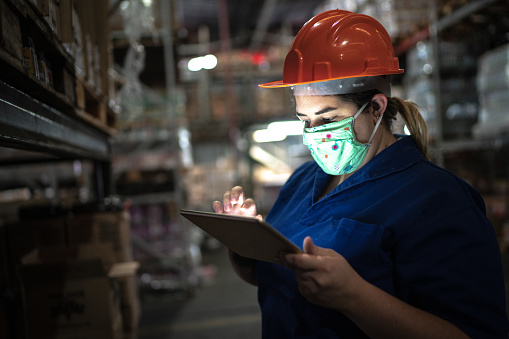Portrait of mid adult woman wearing face mask using digital tablet - working at warehouse / industry 1221804767