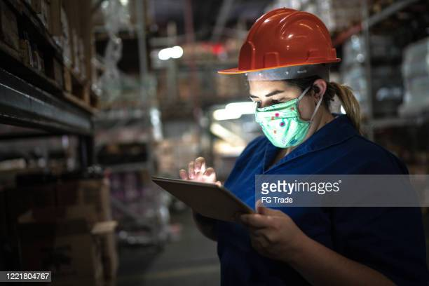 portrait of mid adult woman wearing face mask using digital tablet - working at warehouse / industry - essential workers stock pictures, royalty-free photos & images