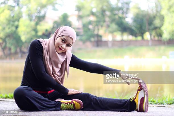 portrait of mid adult woman wearing hijab while exercising by lake at park - 宗教的なベール ストックフォトと画像