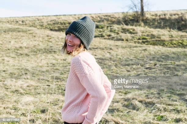 portrait of mid adult woman wearing knitted hat in field - テューリンゲン州 ストックフォトと画像