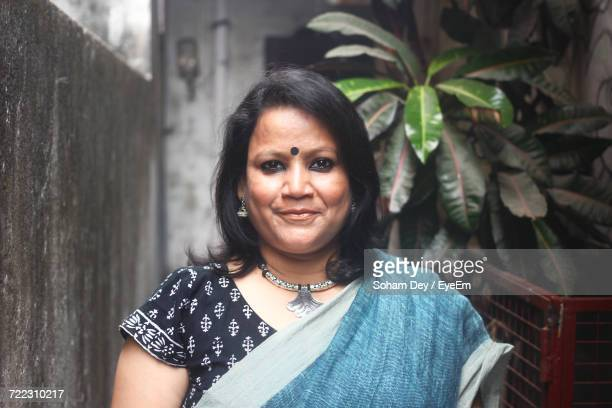 Portrait Of Mid Adult Woman Wearing Sari While Standing In Alley