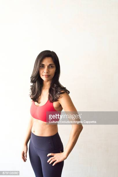 Portrait of mid adult woman wearing sports clothing, hands on hips, studio shot