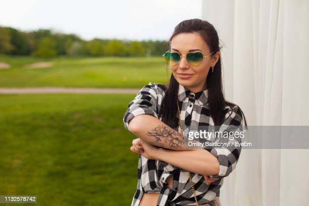 portrait of mid adult woman wearing sunglasses standing on grassy field against sky - tattoo designs hearts stock pictures, royalty-free photos & images