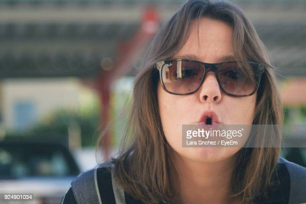 Portrait Of Mid Adult Woman Wearing Sunglasses While Making Face