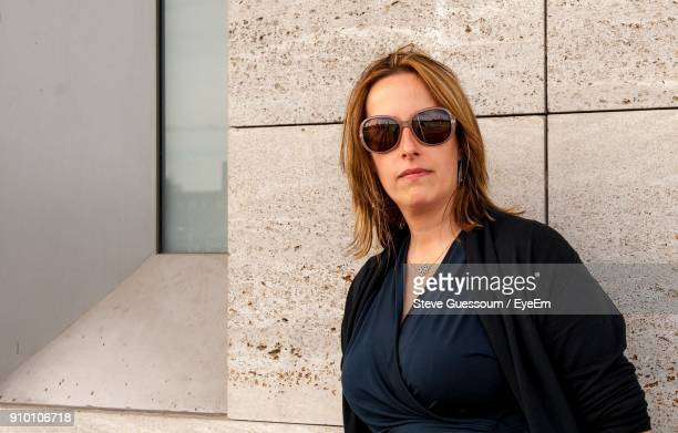 Portrait Of Mid Adult Woman Wearing Sunglasses While Standing Against Wall