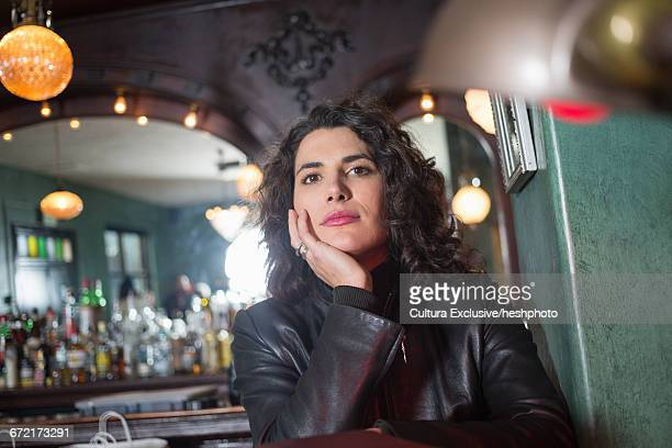 portrait of mid adult woman with chin on hand in recreational bar - heshphoto stock pictures, royalty-free photos & images