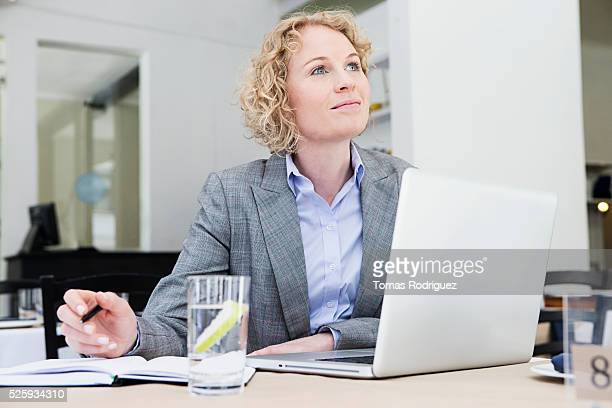 Portrait of mid adult woman with laptop sitting at restaurant table