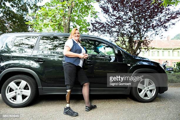 portrait of mid adult woman with prosthetic leg, standing beside car - sigrid gombert imagens e fotografias de stock