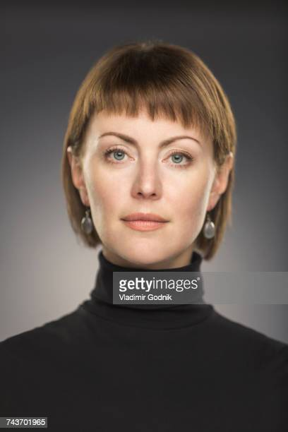 portrait of mid adult woman with short brown hair against gray background - turtleneck stock pictures, royalty-free photos & images