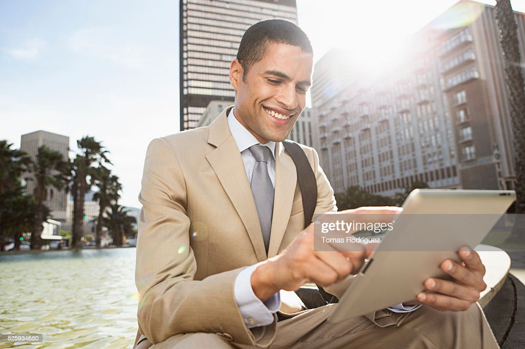 Portrait of mid man sitting by fountain and using digital tablet : Stock Photo