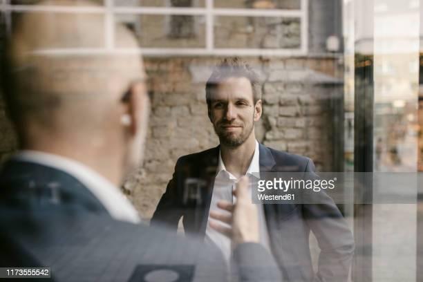portrait of mid-adult businessman and senior having a meeting - 後任 ストックフォトと画像