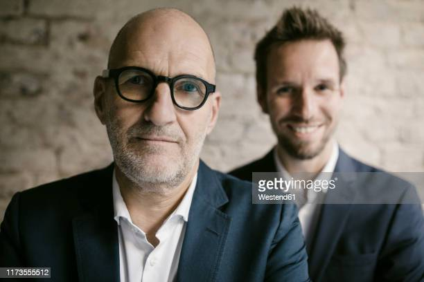portrait of mid-adult businessman behind and senior businessman - two generation family stock pictures, royalty-free photos & images