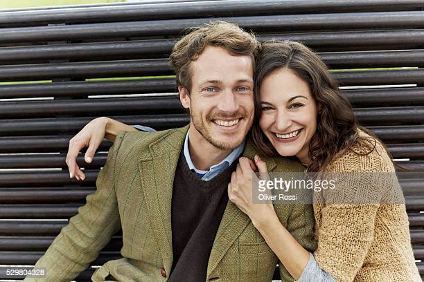 Portrait of mid-adult couple on bench in park