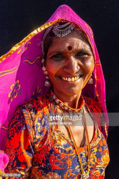 portrait of mid-adult rajasthani woman with pink veil and orange dress, in sunlight, against a black background, pushkar fair, pushkar, rajasthan, india (model release) - james strachan stock pictures, royalty-free photos & images
