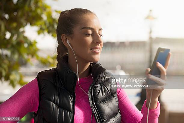 Portrait of mid-adult woman looking at smart phone in city