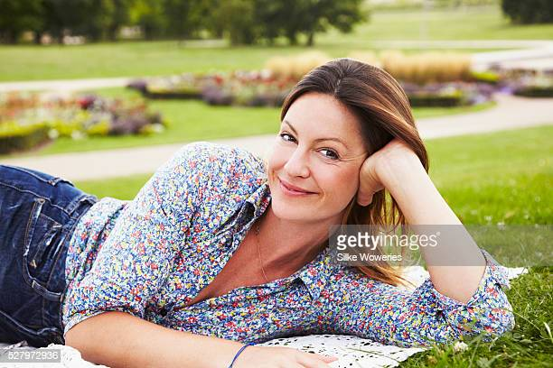 portrait of mid-adult woman lying in park - une seule femme d'âge moyen photos et images de collection