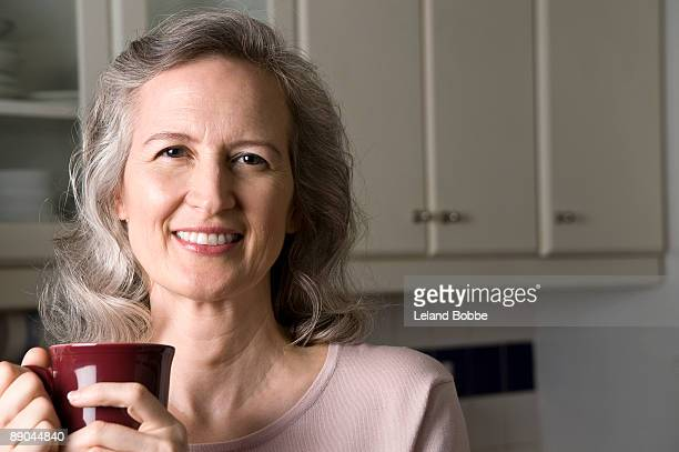 portrait of mid-aged woman holding coffee mug in k