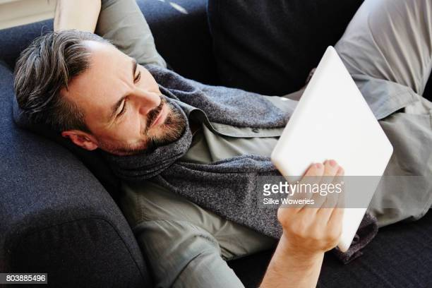 portrait of middle age man laying on the sofa and working on his tablet computer