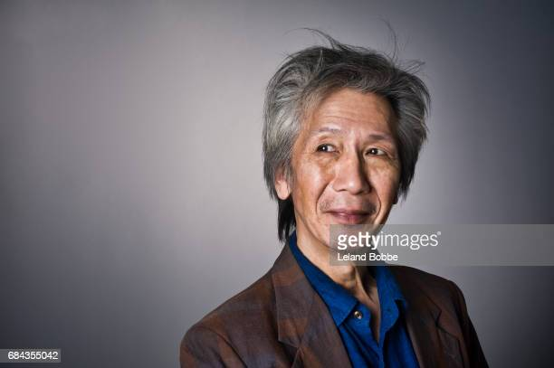 portrait of middle aged asian male with grey hair - royal blue stock pictures, royalty-free photos & images