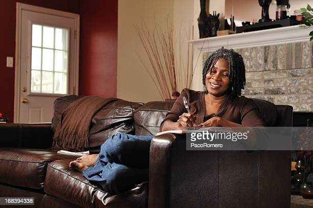 portrait of middle aged black woman writing at home - diary stock pictures, royalty-free photos & images