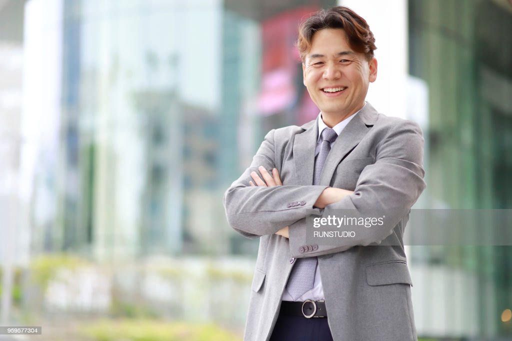 Portrait of middle aged businessman with arms folded outdoors : Stock-Foto