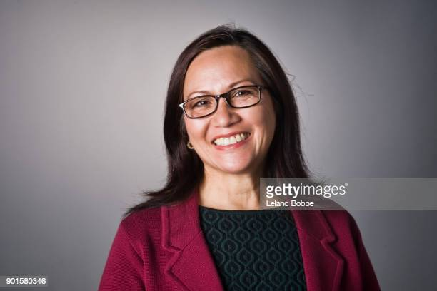 portrait of middle aged filipino woman - gray background stock pictures, royalty-free photos & images