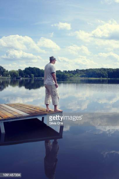 Portrait of middle aged man on jetty looking over lake on a sunny day