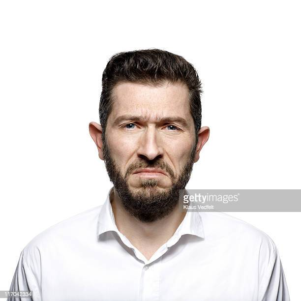 portrait of middle aged man with beard looking sad - misnoegd stockfoto's en -beelden