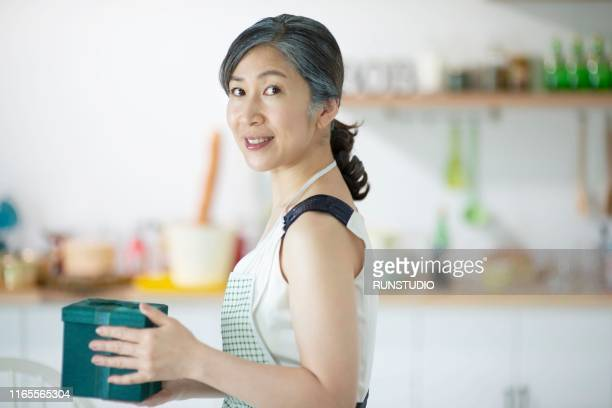 portrait of middle aged woman holding gift box - 専業主婦 ストックフォトと画像