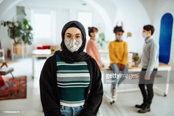 portrait d'un entrepreneur du moyen-orient - coworking pendant la pandémie de coronavirus - hijab feet photos et images de collection