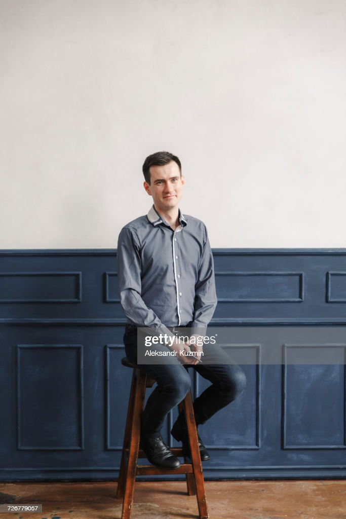 Portrait of Middle Eastern man sitting on stool : Stock Photo