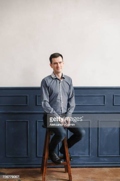 Portrait of Middle Eastern man sitting on stool