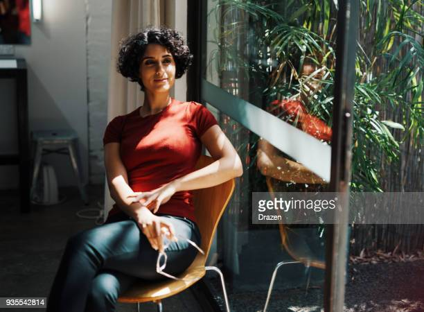 portrait of middle eastern young woman at home near window - assertiveness stock pictures, royalty-free photos & images