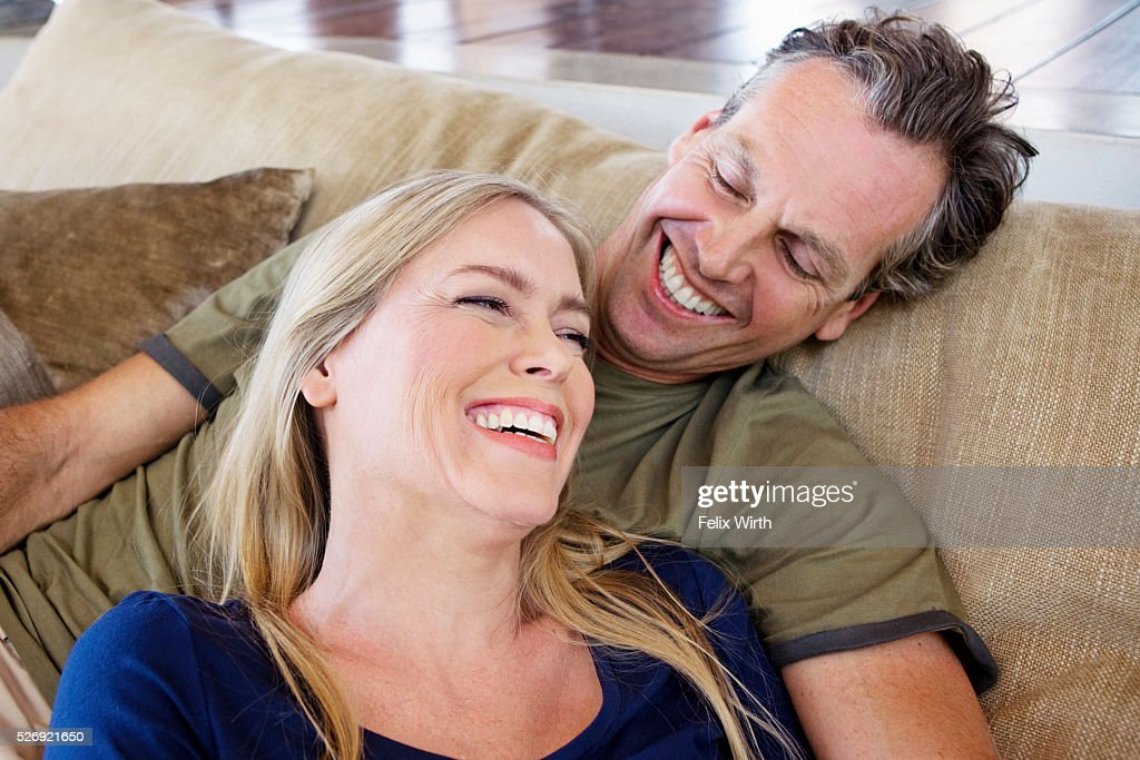 Portrait of middle-aged couple sitting on sofa : Stockfoto