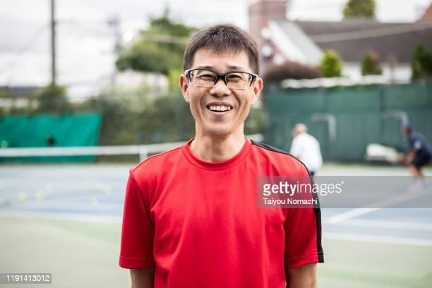 portrait of middle-aged man enjoying tennis - 選手  ストックフォトと画像
