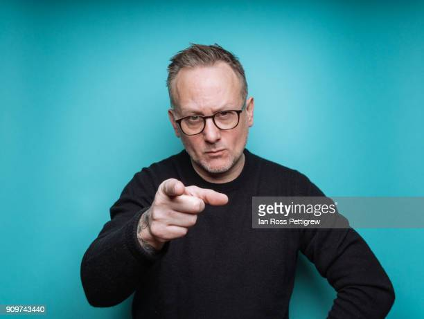 portrait of middle-aged man on blue background pointing - dedo humano imagens e fotografias de stock