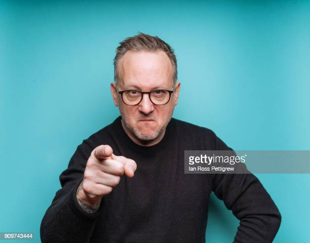 portrait of middle-aged man on blue background pointing - misnoegd stockfoto's en -beelden